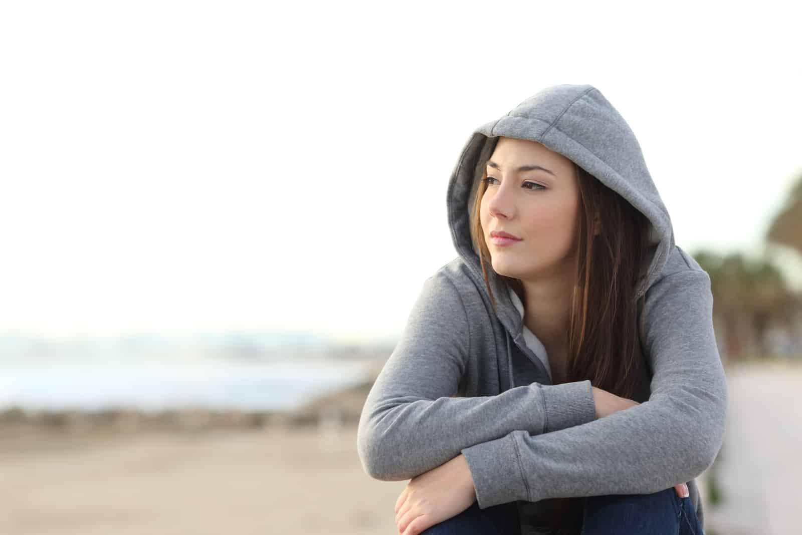 nachdenklicher Teenager sitzt am Strand und schaut weg