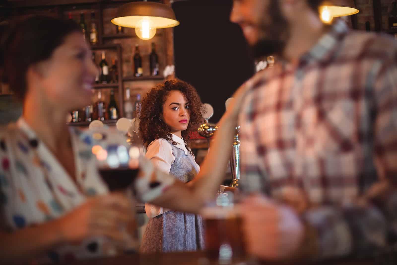 traurige Frau, die ein liebendes Paar in der Bar sucht