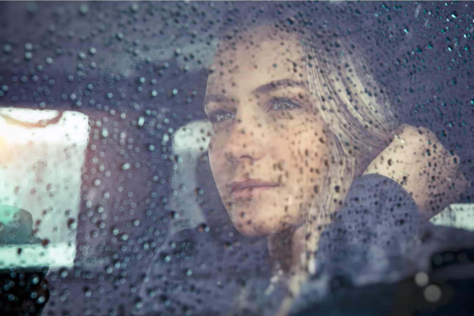 traurige Frau, die im Auto bei Regenwetter sitzt