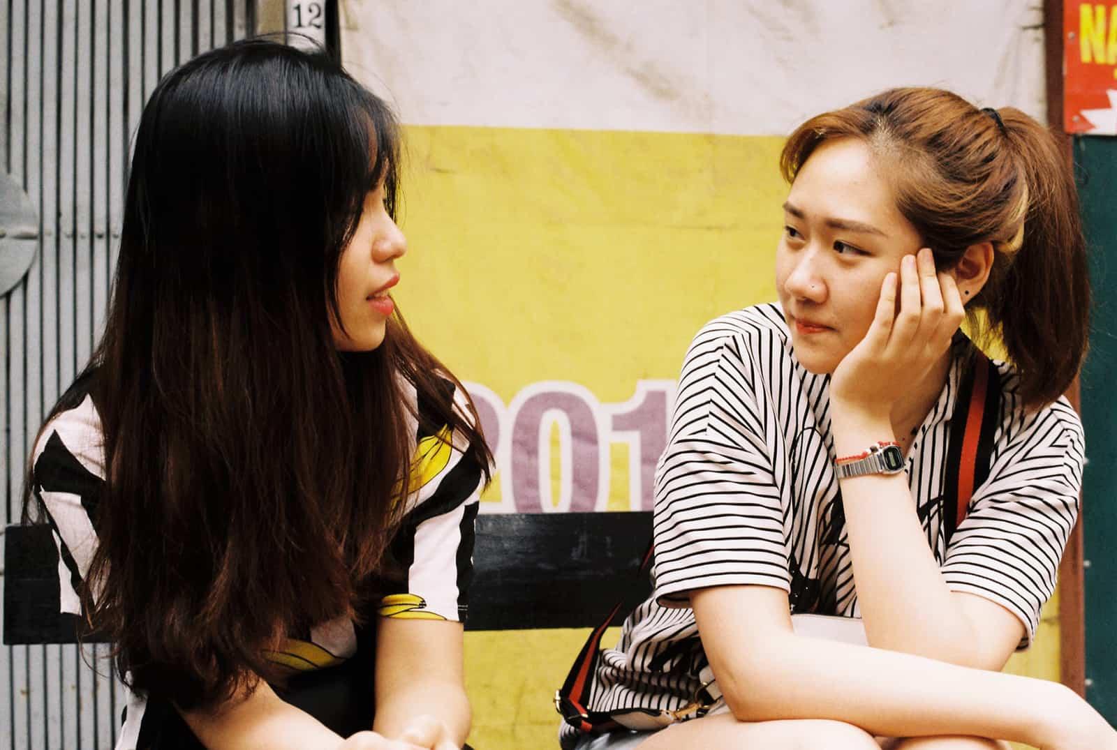 zwei Frauen reden und sitzen auf der Bank