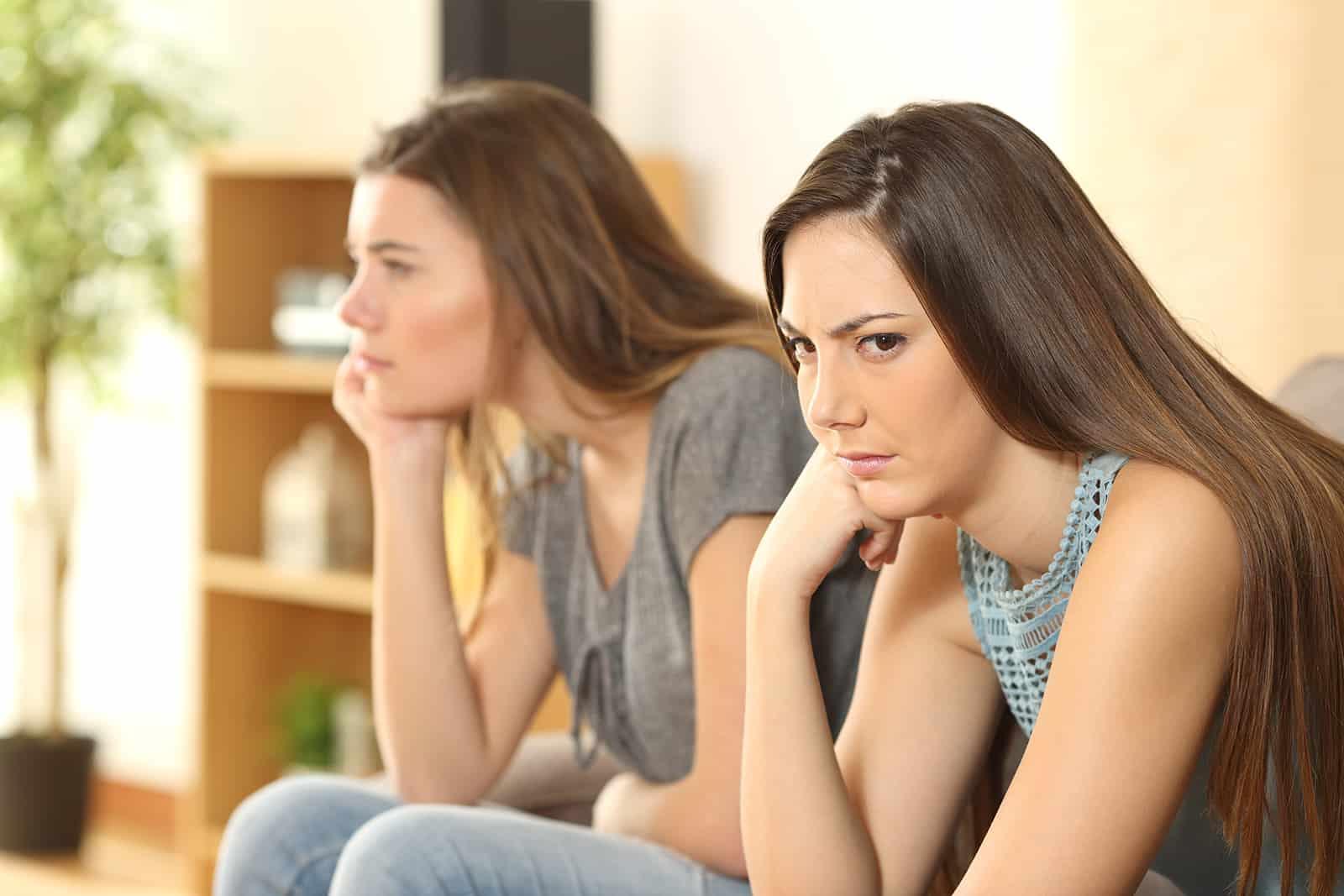 zwei verärgerte Freundinnen sitzen auf der Couch und ignorieren sich gegenseitig