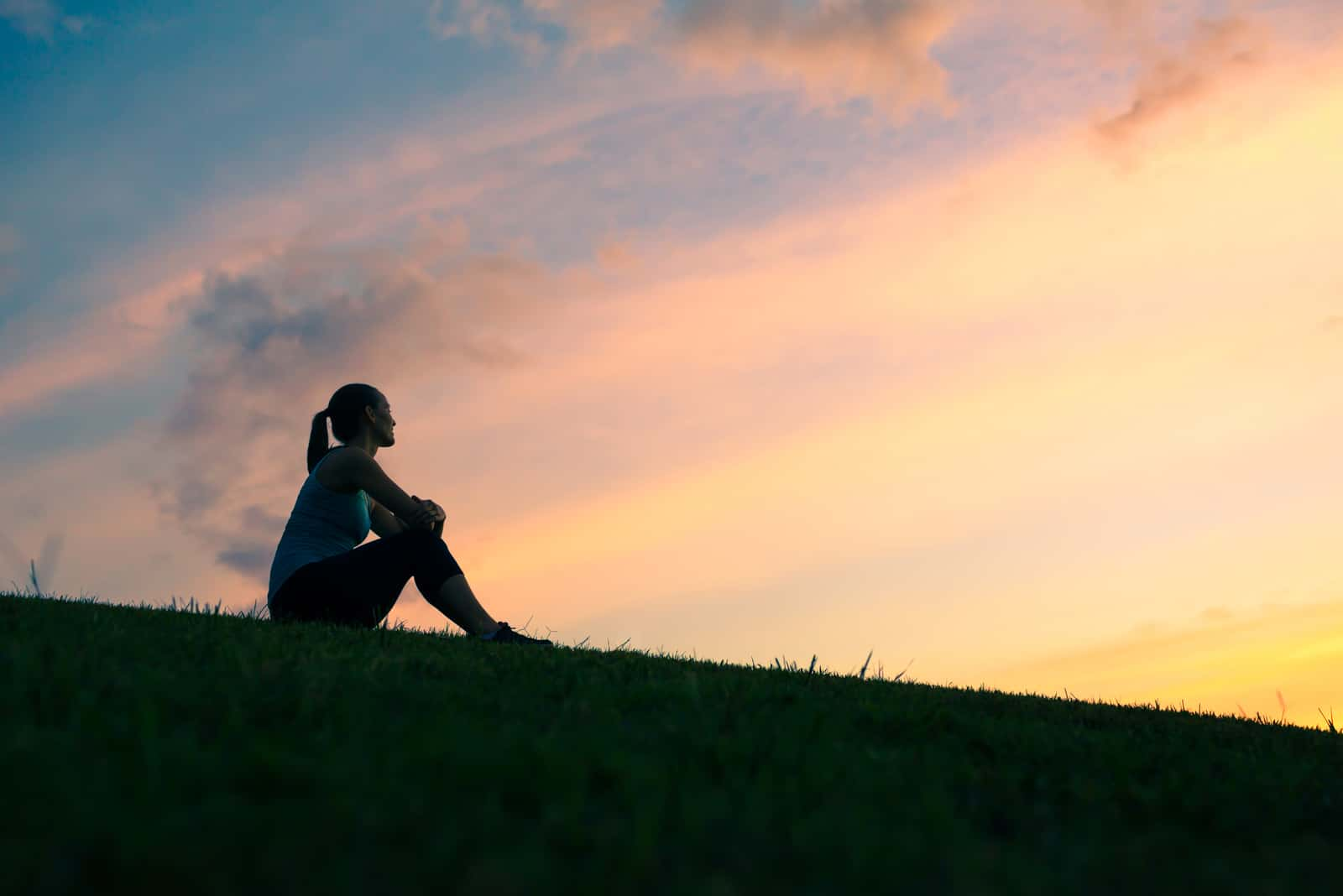 Allein sitzende Frau, die den Sonnenuntergang beobachtet