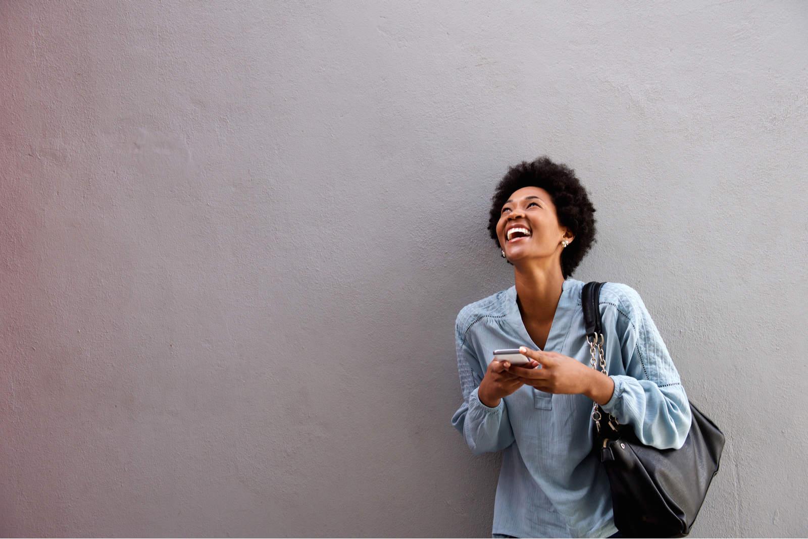 eine lächelnde Frau mit einem Telefon in der Hand