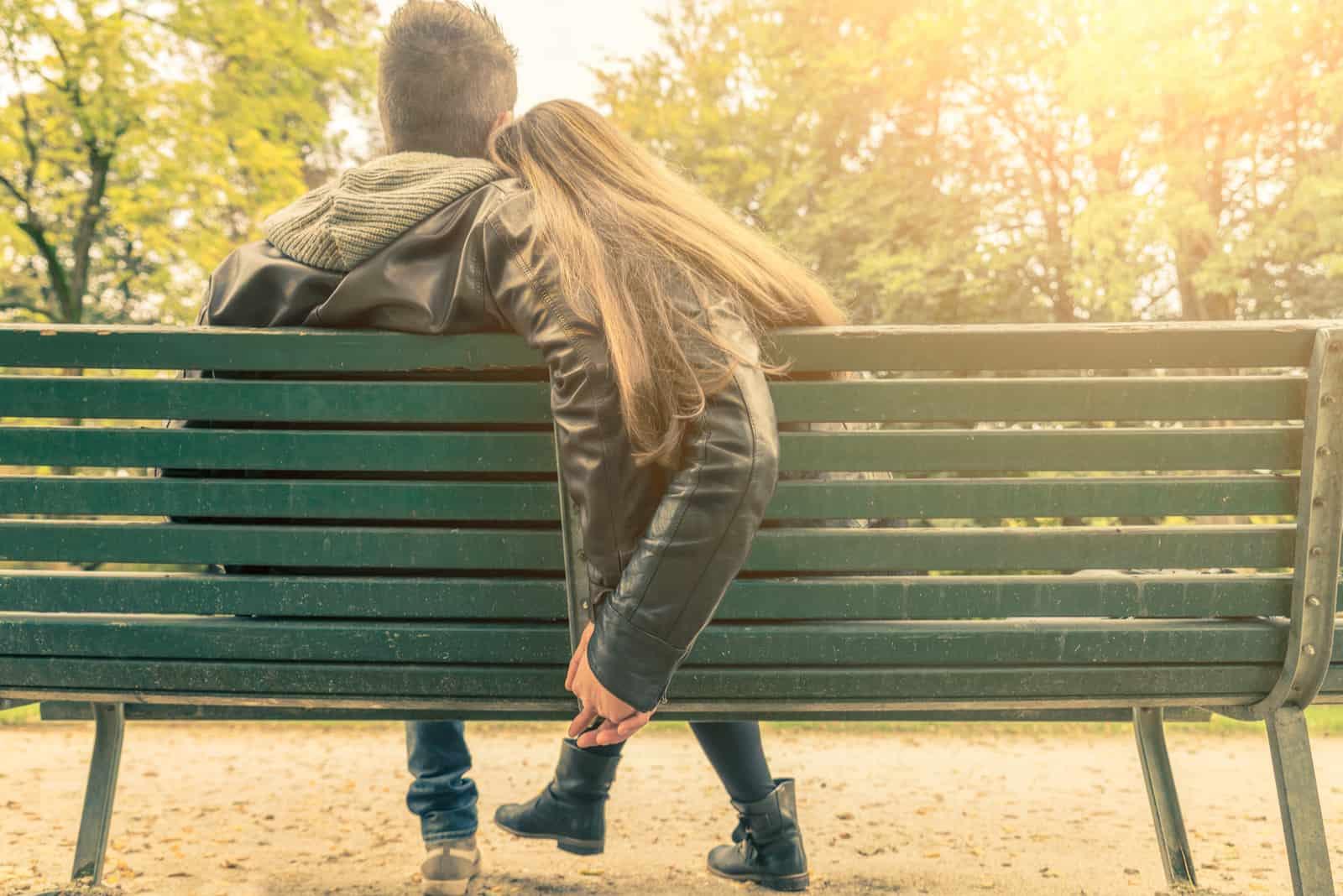 Auf einer Parkbank sitzt ein verliebtes Paar