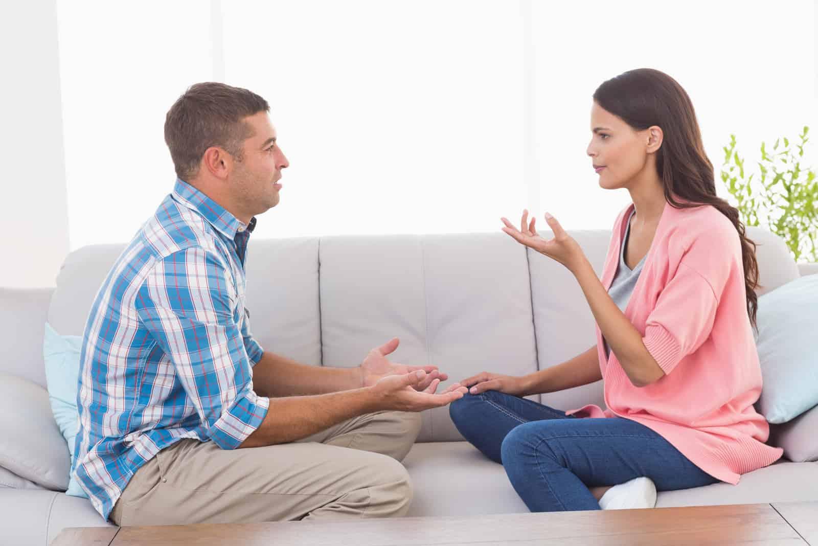 Das Paar auf dem Sofa sitzt und streitet