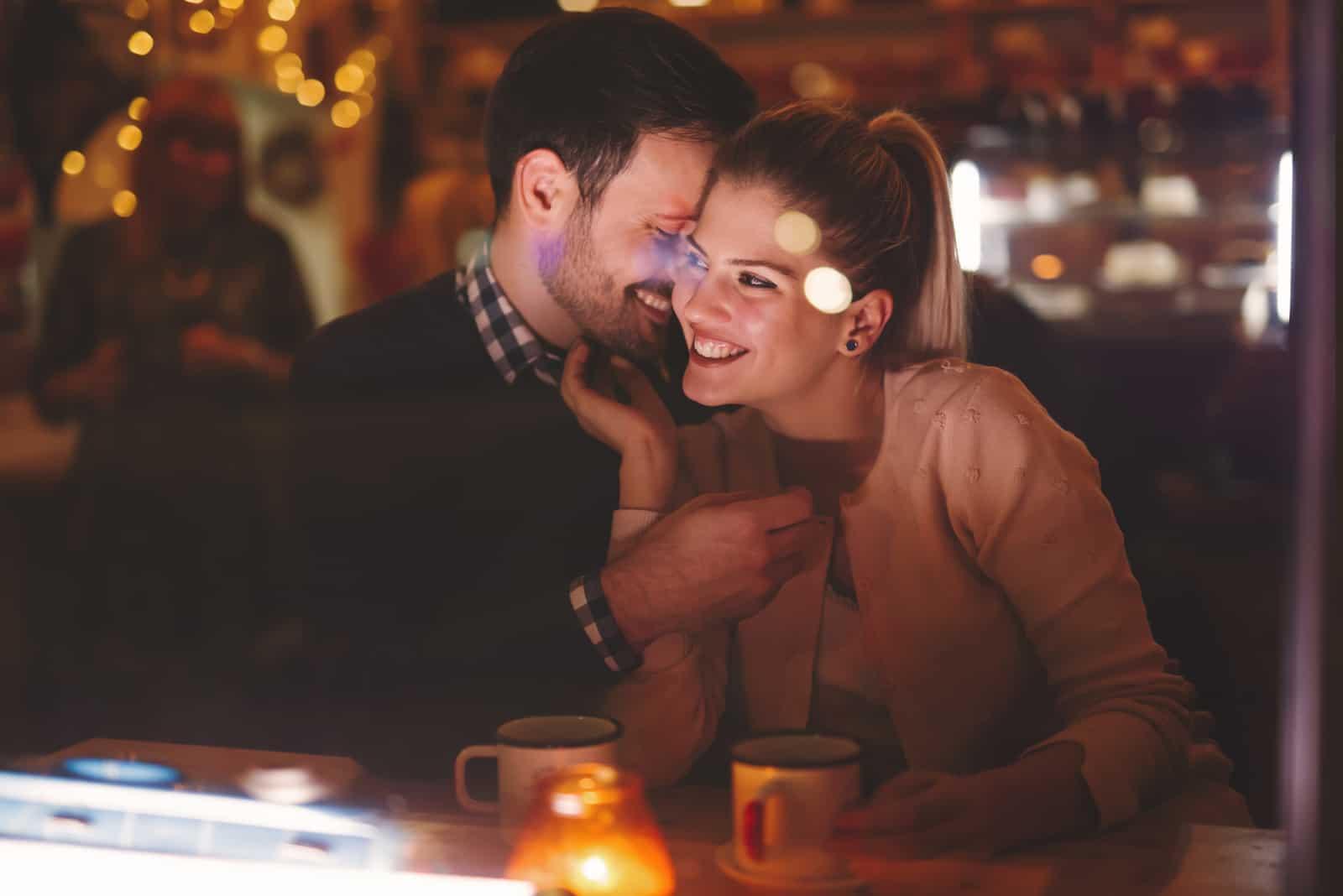 Der Mann flüstert der Frau ins Ohr und lacht, als sie im Restaurant sitzen