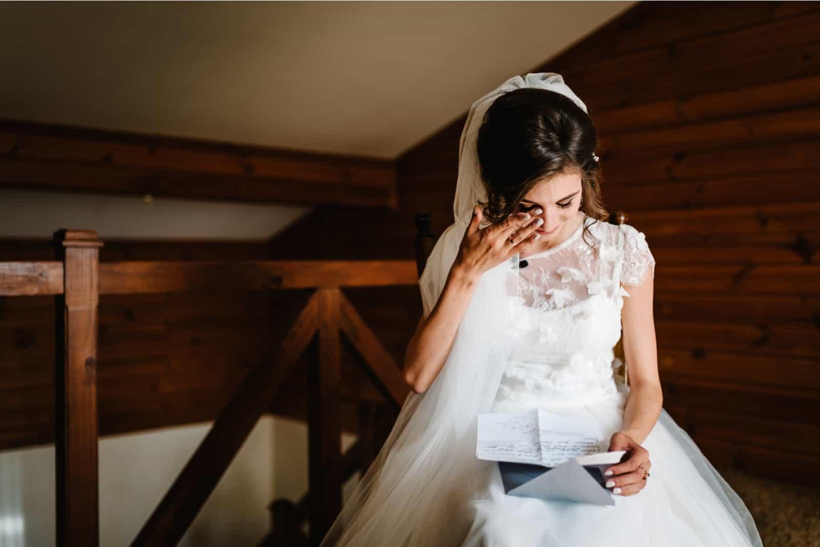 Die Frau im Hochzeitskleid liest den Brief und weint