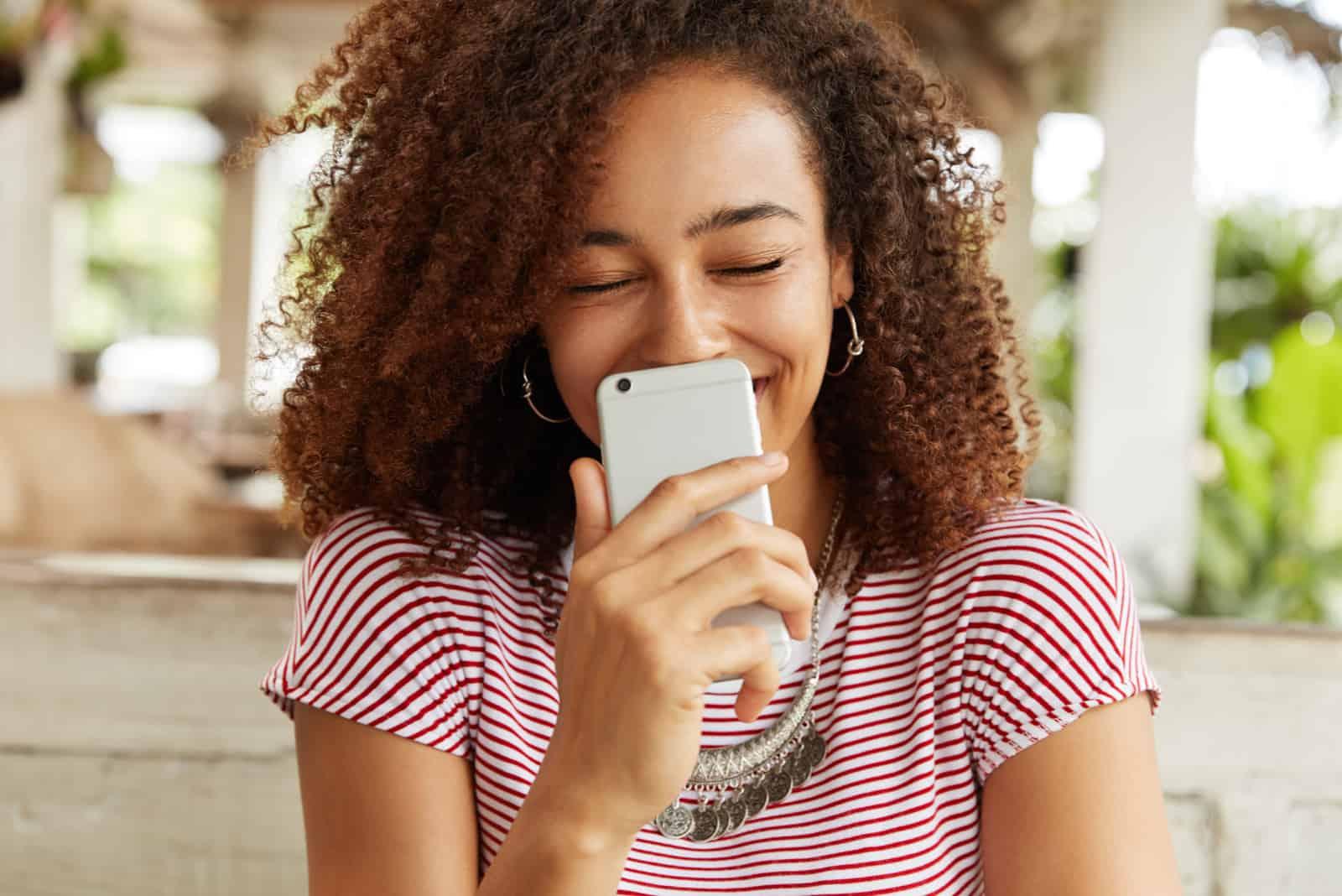 Die Frau weint vor Glück, als sie das Telefon in der Hand hält