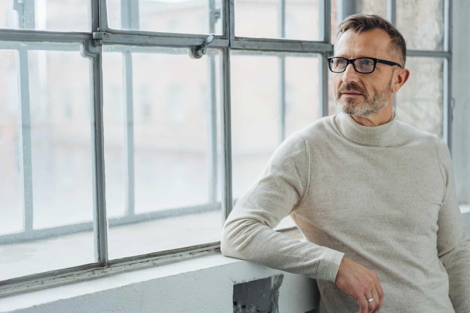 Mann der eine Brille trägt, die durch Fenster steht