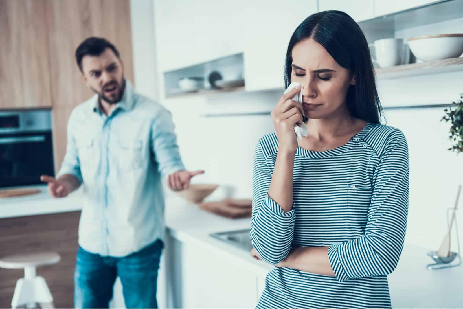 Ein Mann in der Küche schreit seine traurige Frau an