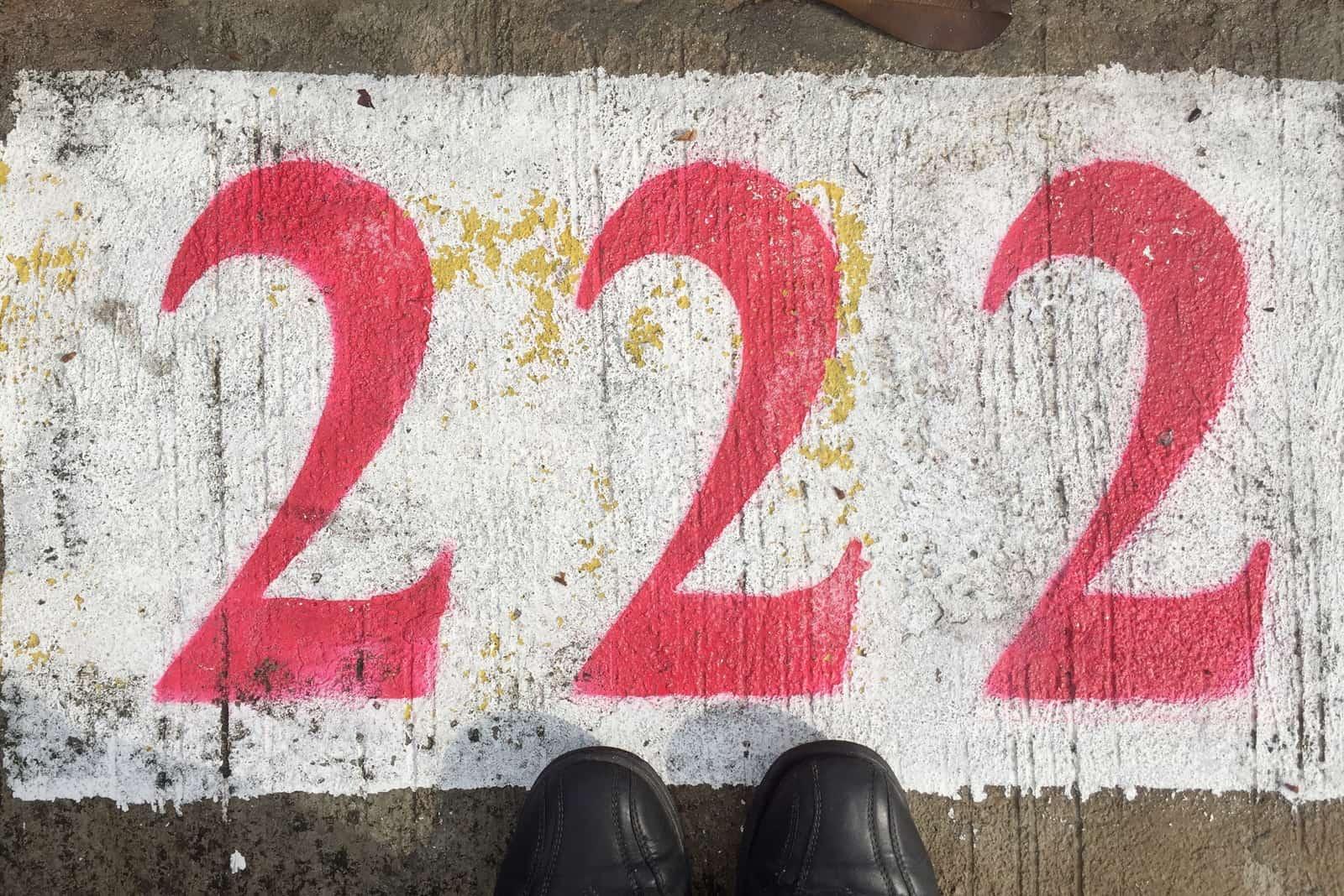 Ein Mann steht auf dem Beton neben der Inschrift 222