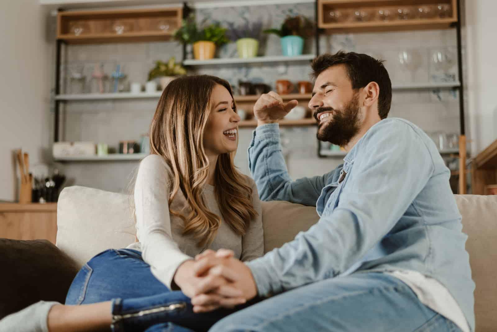 Ein Mann und eine Frau halten sich an den Händen, während sie auf der Couch sitzen und lachen und reden