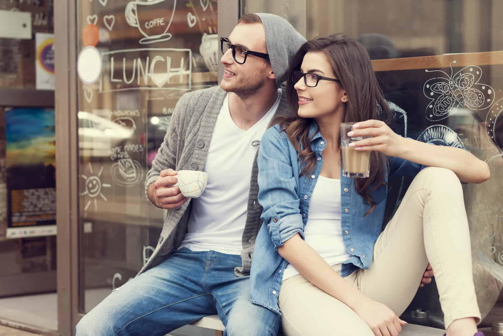 Ein Mann und eine Frau sitzen beim Kaffeetrinken und schauen in die Ferne