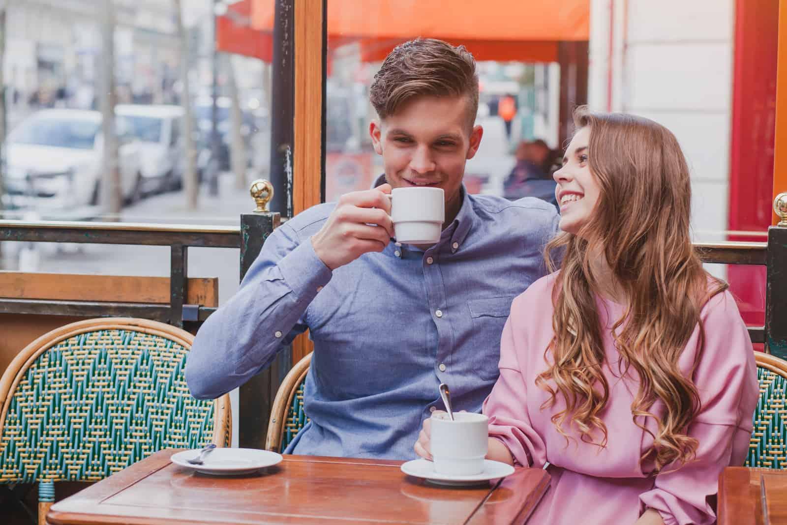 Ein Mann und eine Frau sitzen, trinken Kaffee und lachen