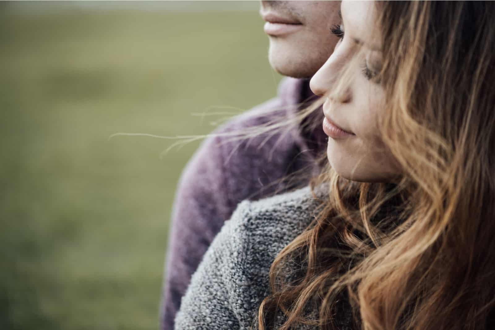 Ein Mann und eine Frau umarmen sich und schauen in die Ferne