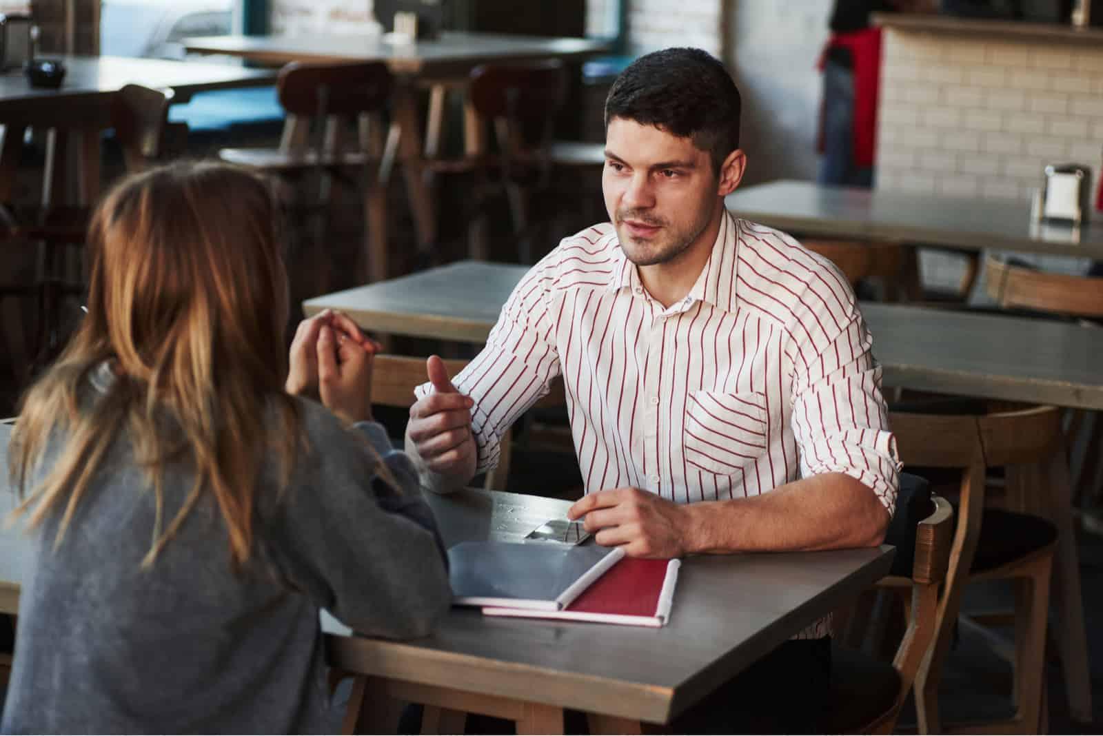 Ein Mann und eine Frau unterhalten sich, während sie sich gegenüber sitzen