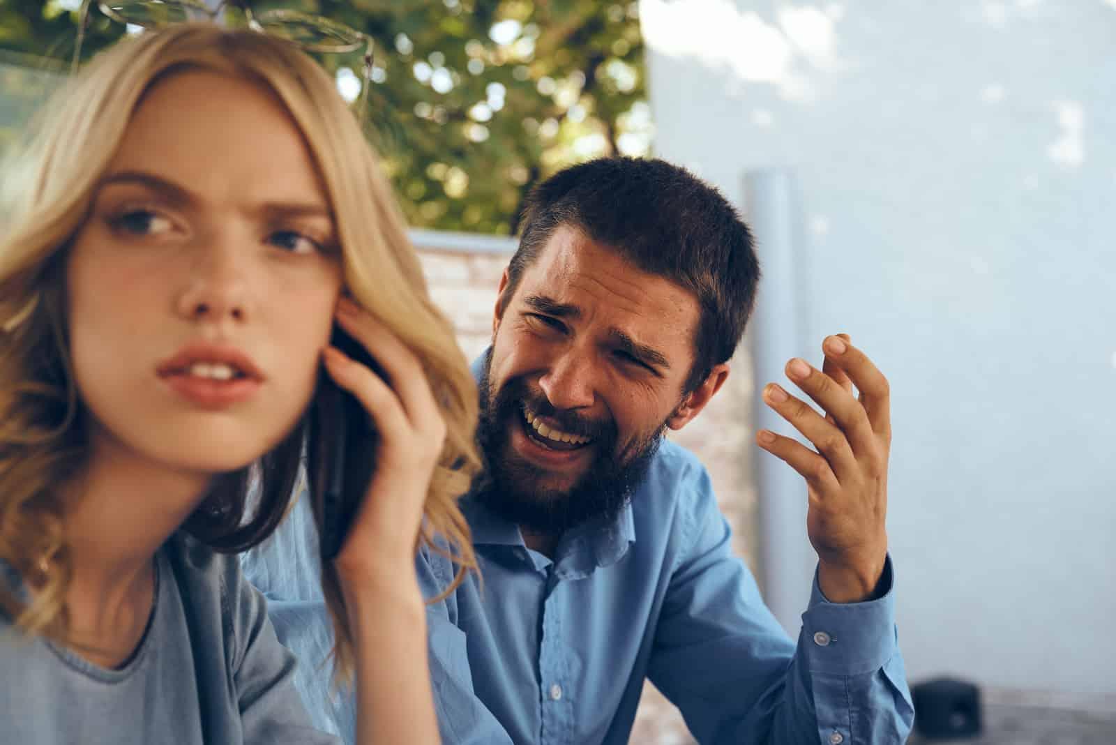 Ein bärtiger Mann kritisiert eine traurige Frau