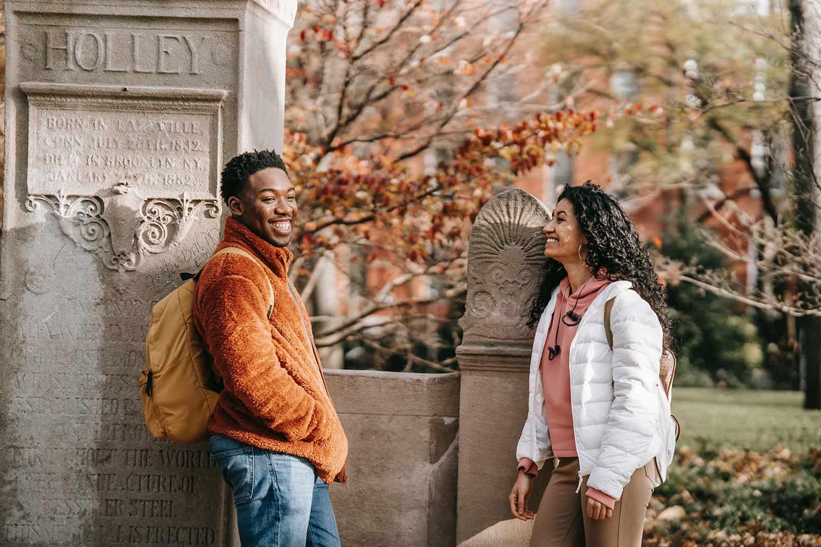 Ein fröhlicher Mann und eine Frau stehen im Park und reden