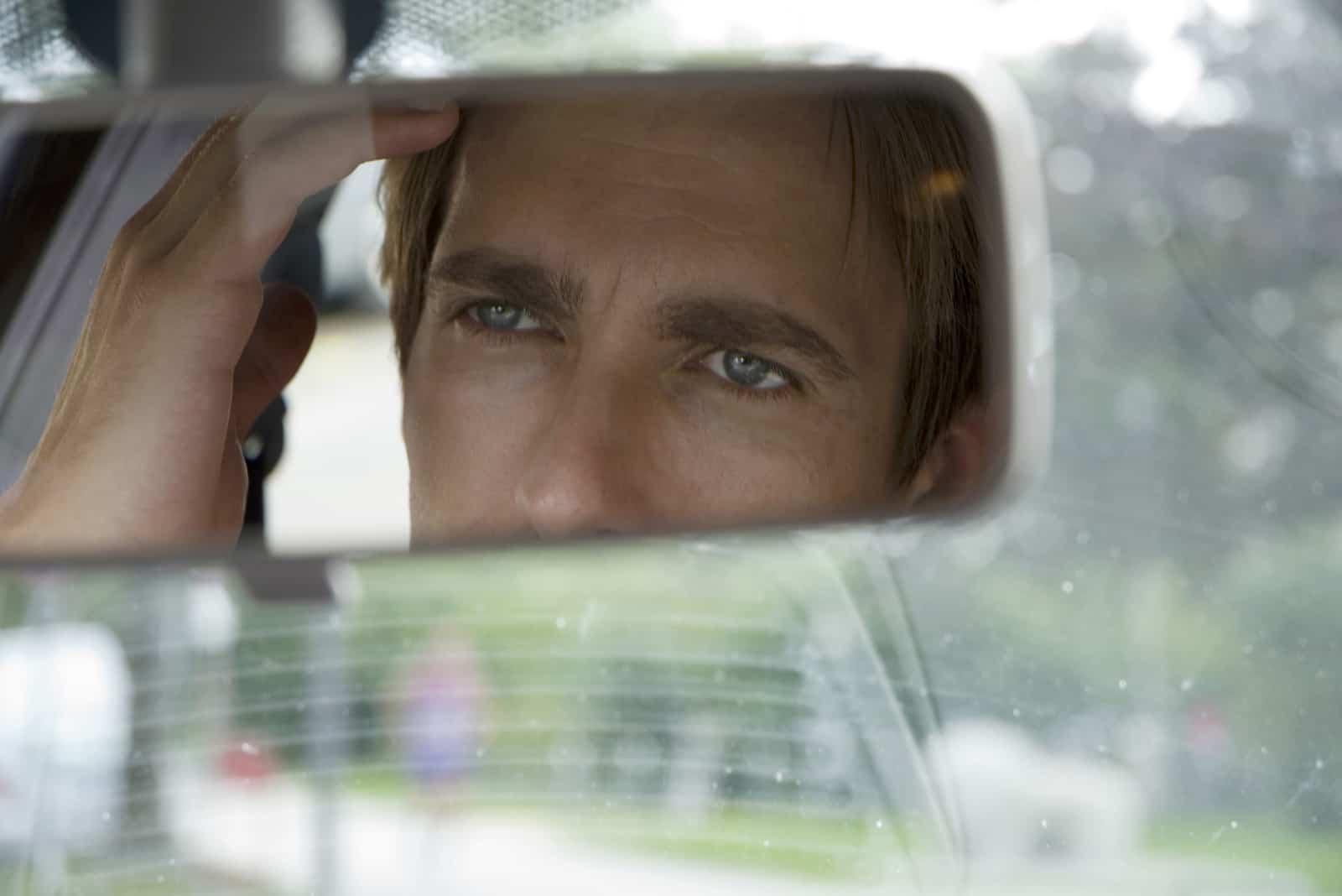 Ein gutaussehender Mann schaut im Auto in den Spiegel