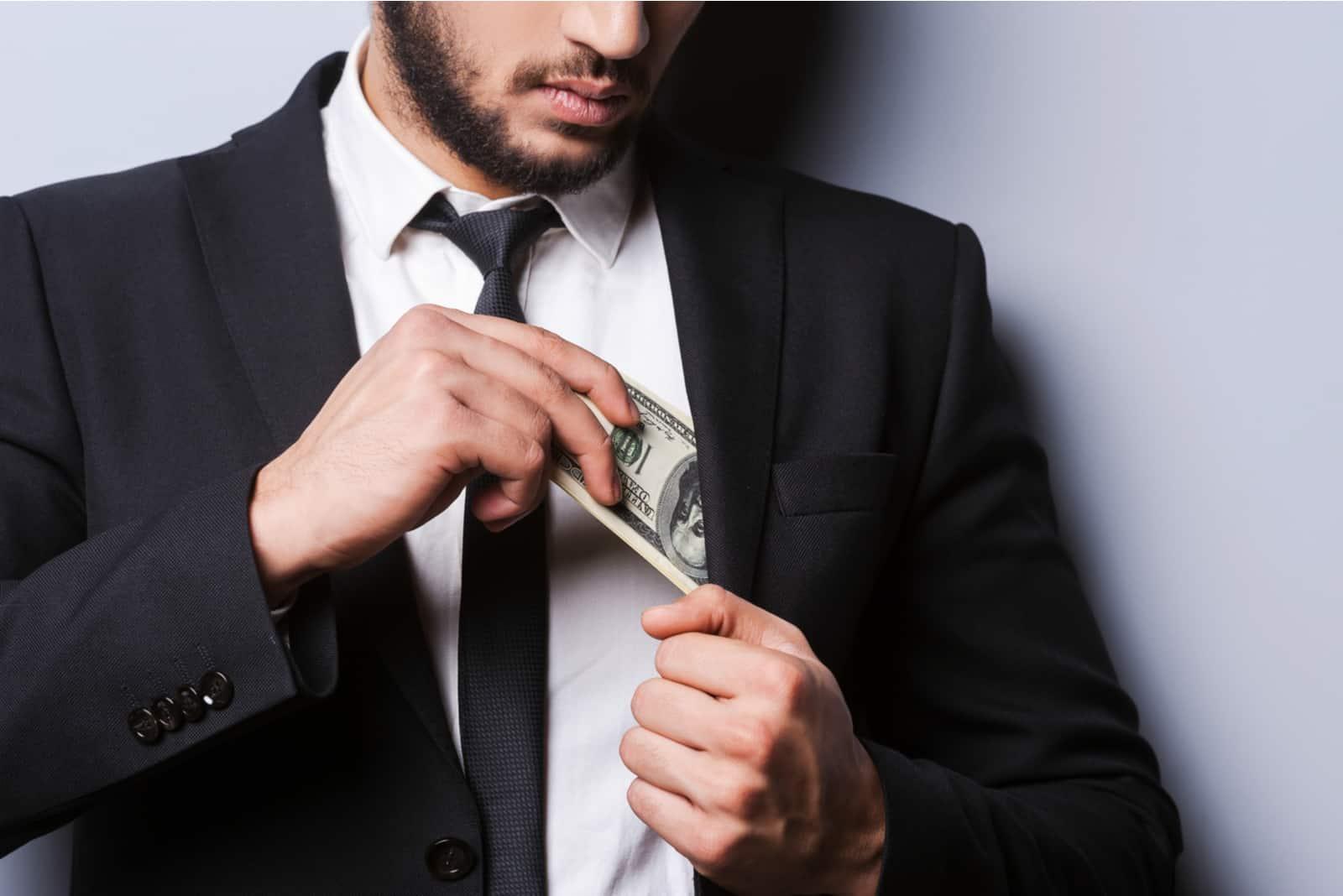 Ein gutaussehender bärtiger Mann steckt Geld in seine Jackentasche