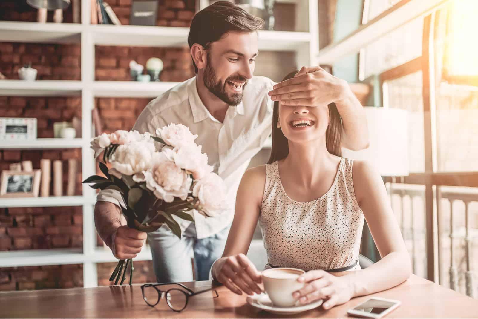 Ein hübscher bärtiger Mann überreicht einem lächelnden Mädchen einen Rosenstrauß