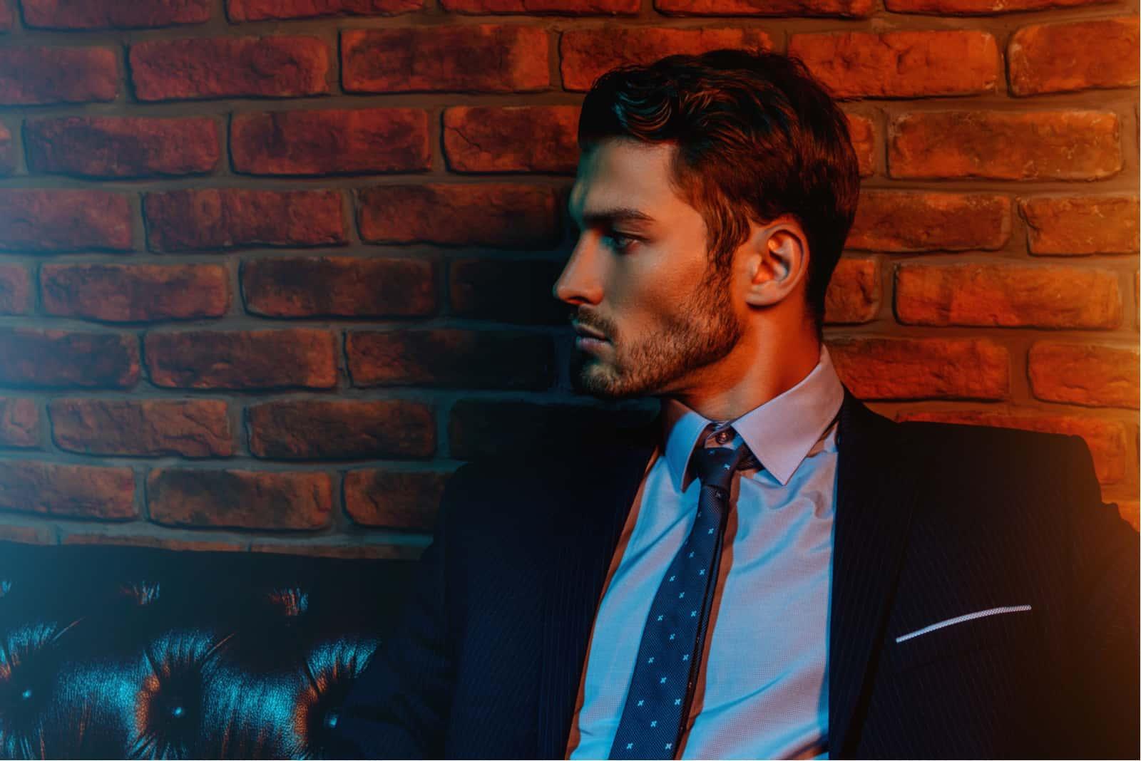 Ein hübscher, eleganter Mann sitzt auf einem Ledersofa