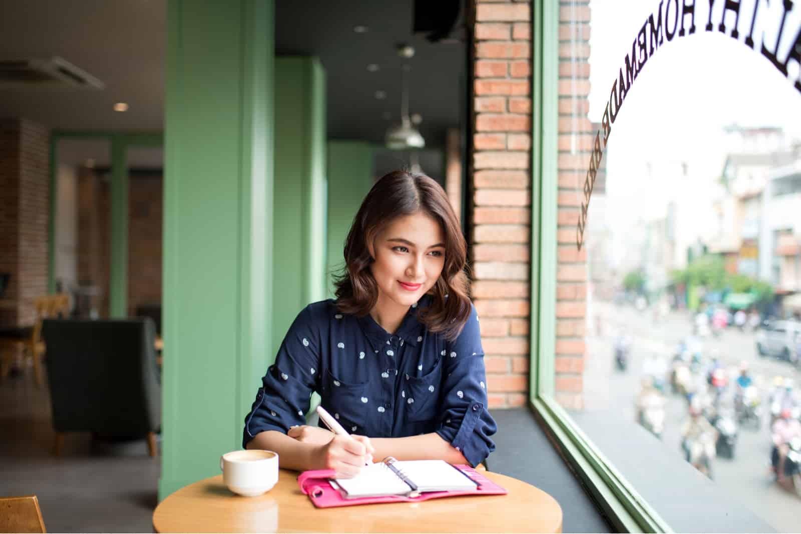 Eine Frau, die mit Kaffee an einem Tisch sitzt, schreibt