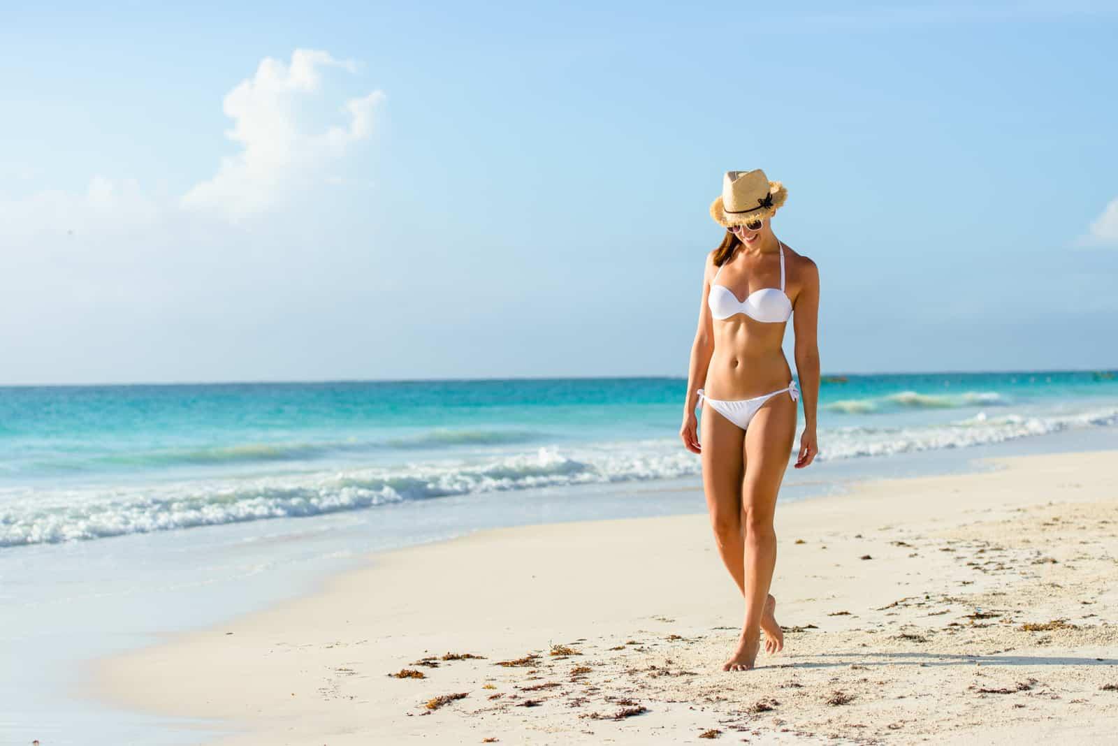 Eine Frau im Badeanzug setzt den Strand