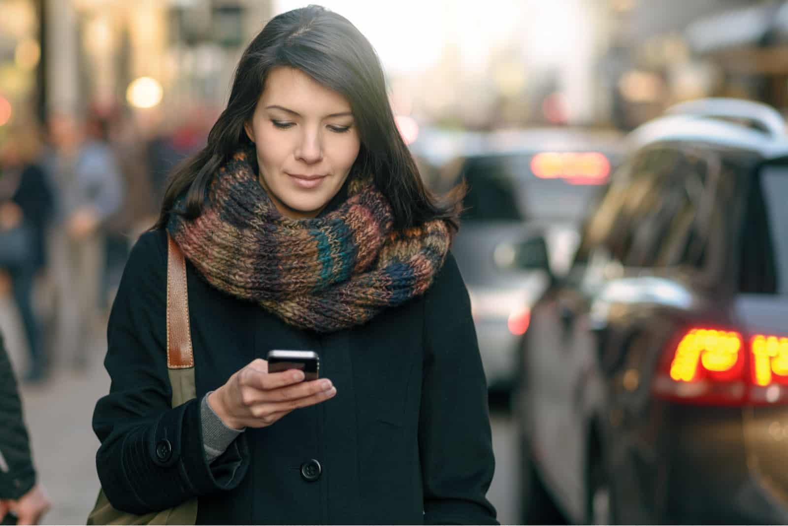 Eine Frau in einem schwarzen Mantel geht die Straße entlang und sendet eine SMS auf ihr Smartphone
