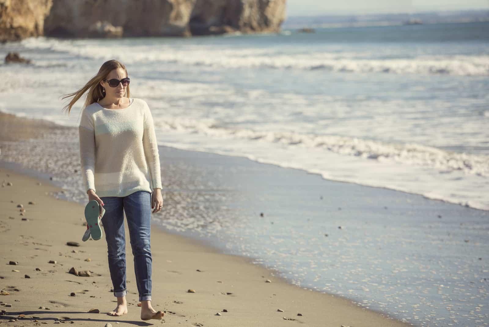 Eine Frau mit langen braunen Haaren sitzt am Strand