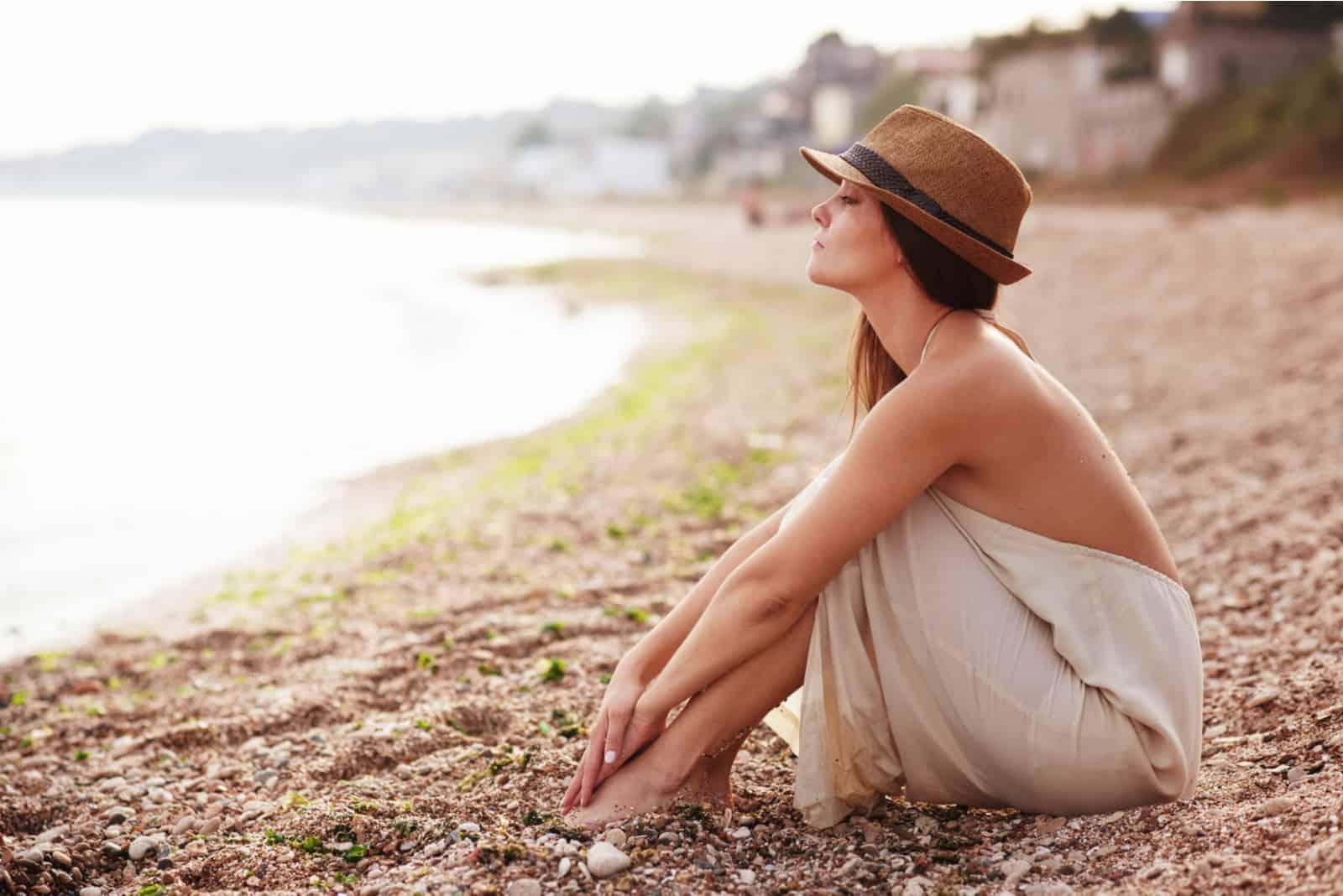 Eine Frau mit langen braunen Haaren und einem Hut auf dem Kopf sitzt am Strand