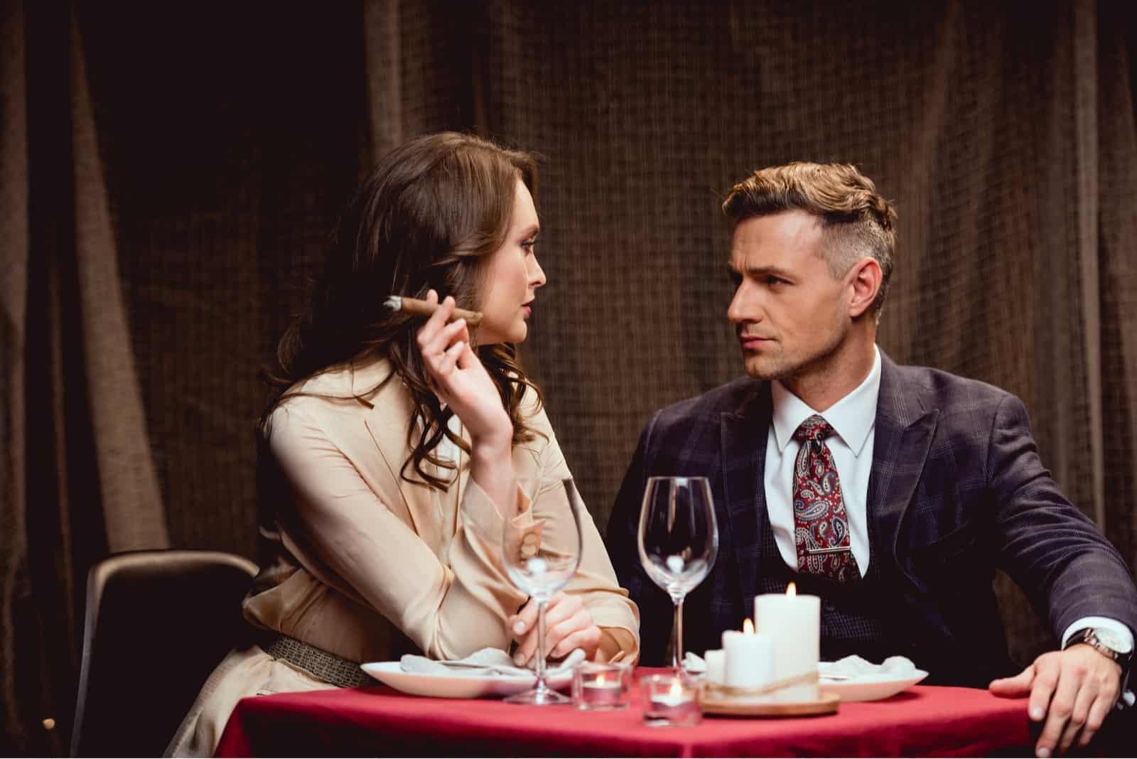Eine Frau und ein Mann sitzen an einem Tisch, während sie eine Zigarre rauchen