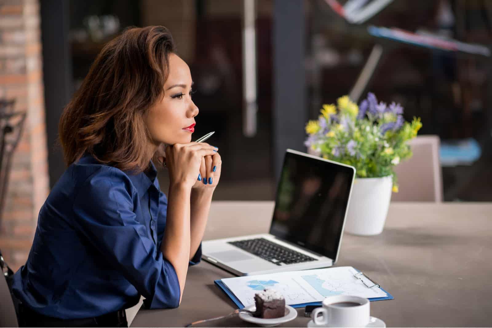 Eine Geschäftsfrau sitzt an einem Schreibtisch im Büro und denkt nach