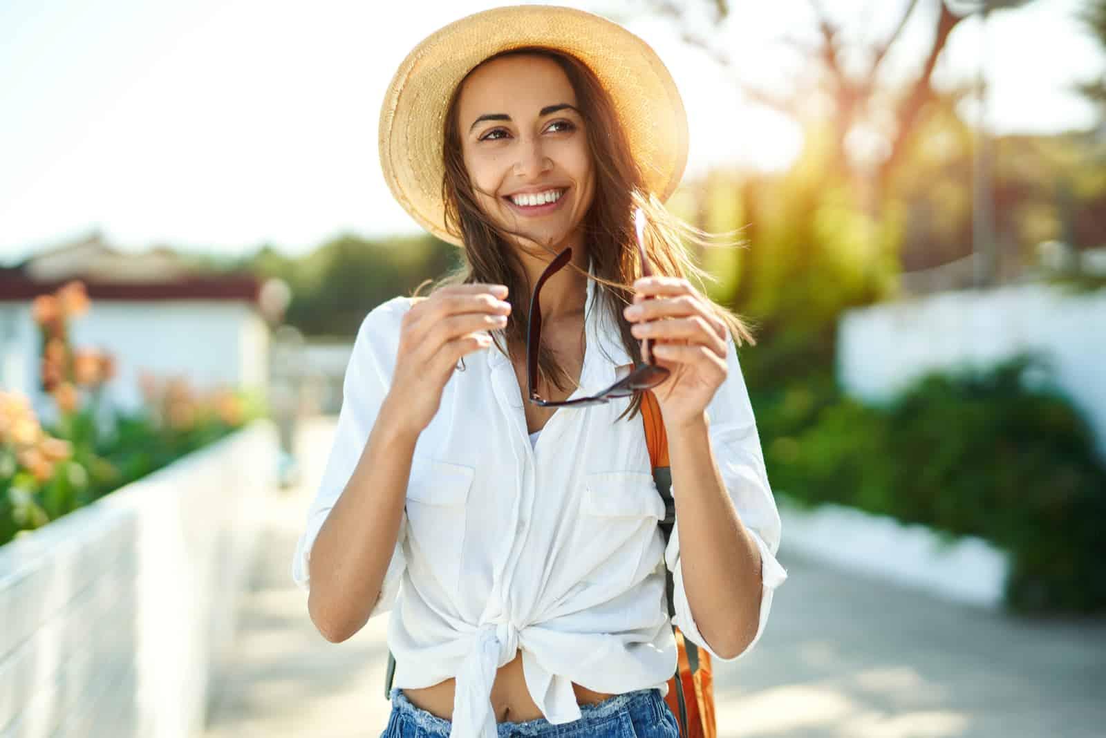 Eine braunhaarige Frau mit einem Hut auf dem Kopf geht die Straße entlang und lacht