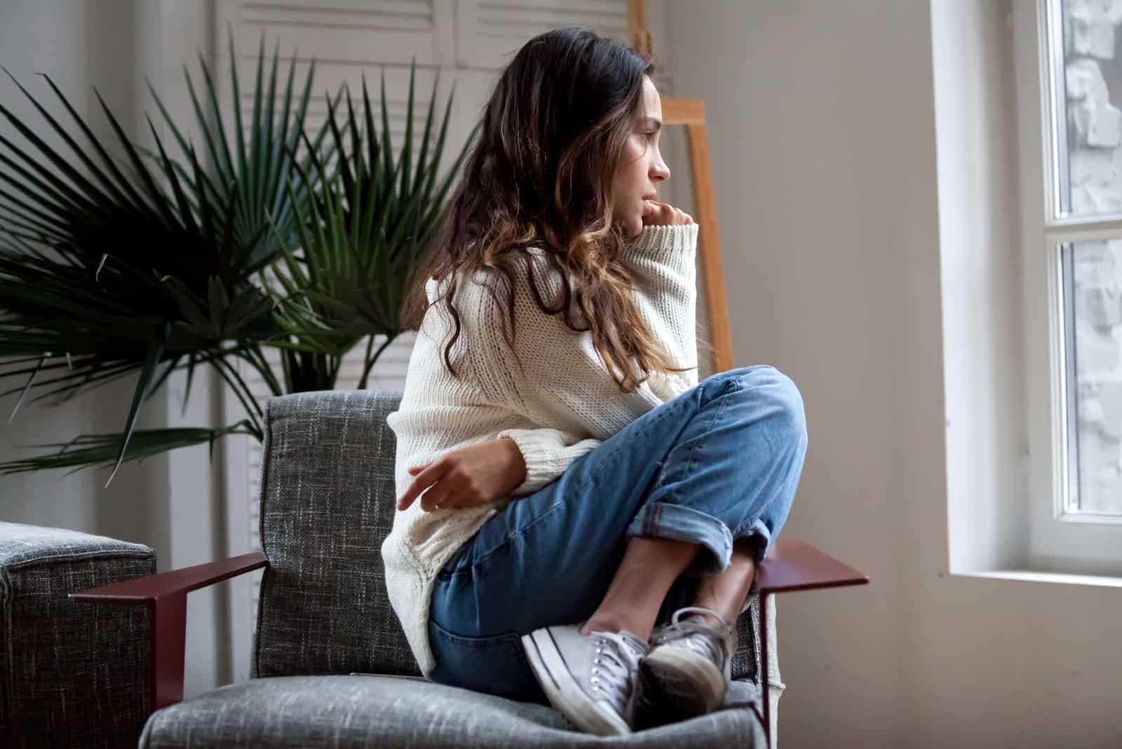 Eine depressive Frau sitzt in einem Sessel