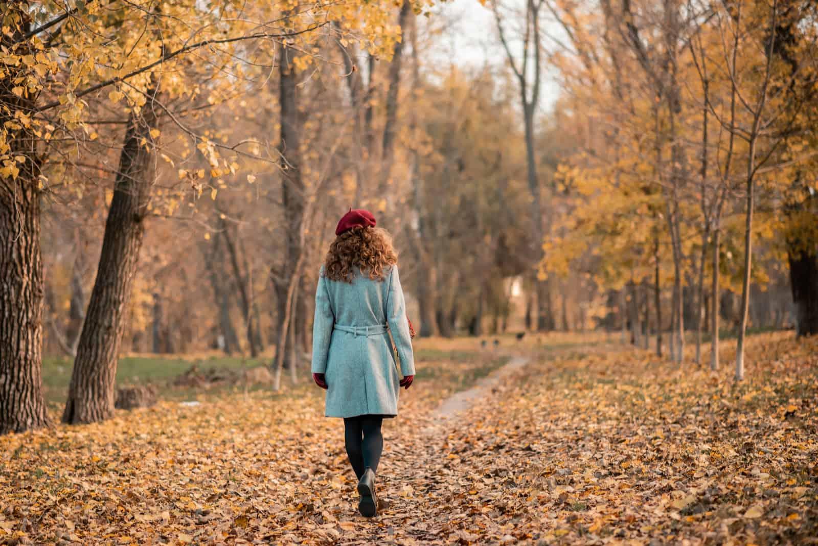 Eine junge Frau mit krausem Haar setzt sich in den Wald