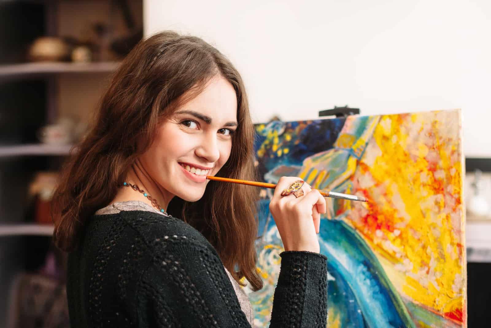 Eine lächelnde Frau malt ein Bild
