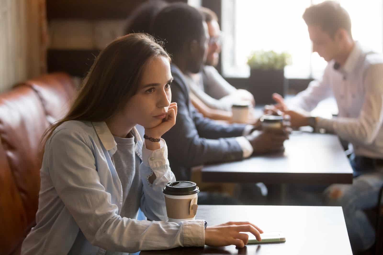 Eine nachdenkliche Frau sitzt in einem Café und wartet auf jemanden