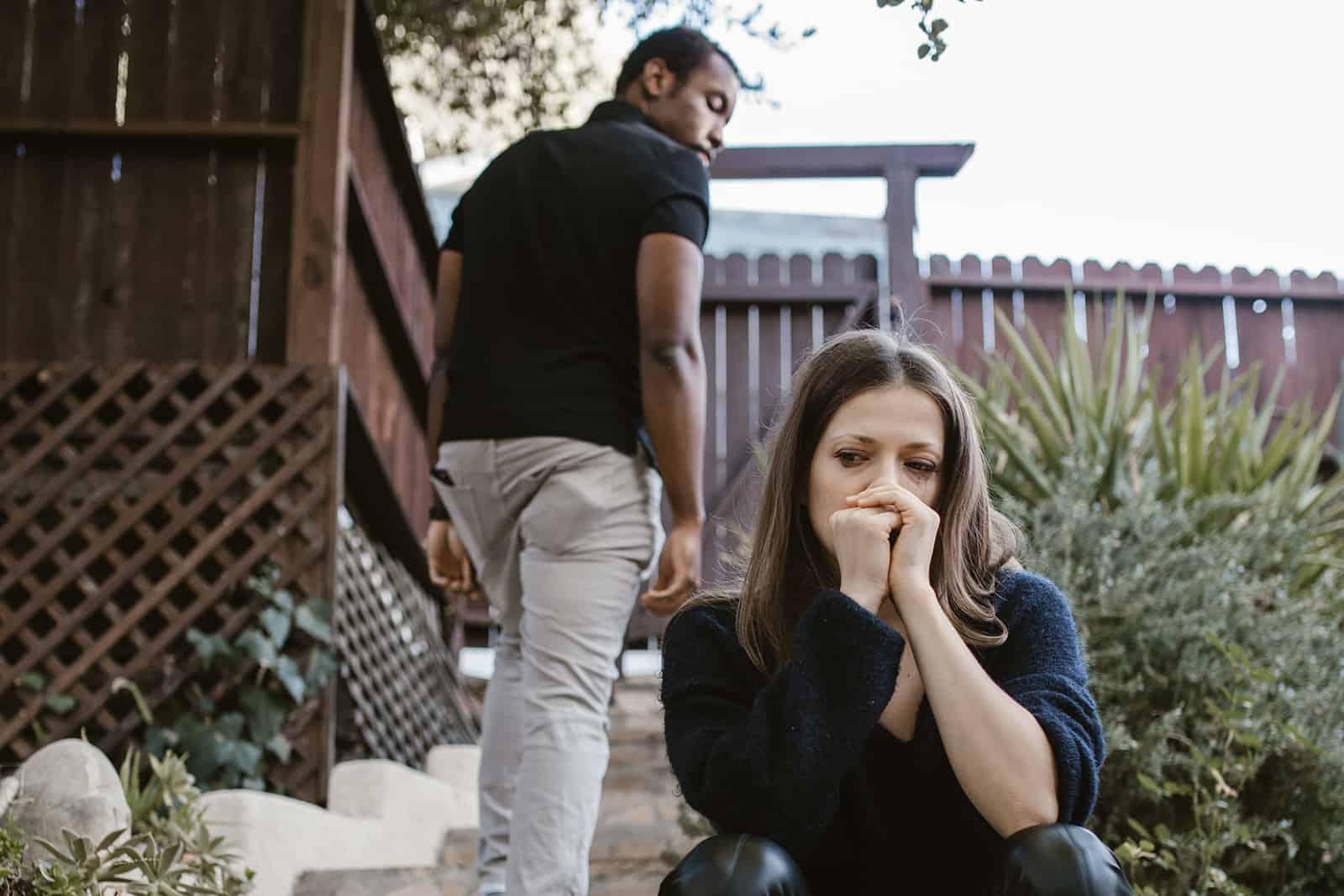 traurige Frau, die auf der Treppe sitzt, während ein Mann sie verlässt