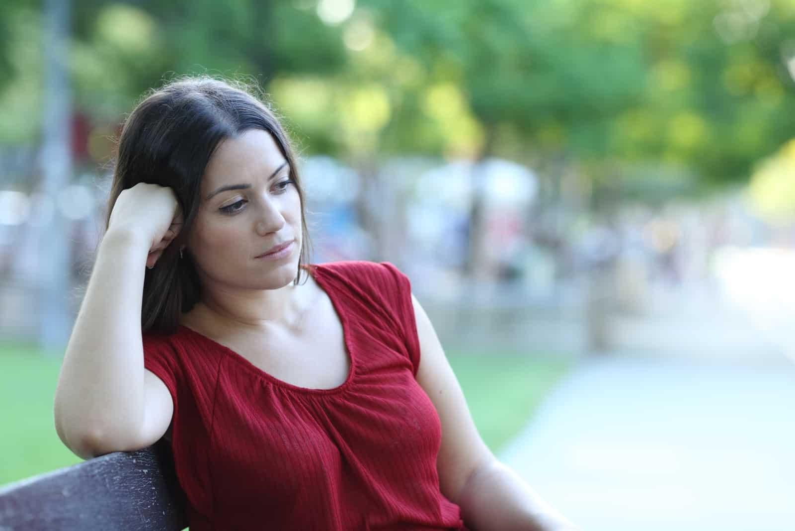 Frau sitzt auf einer Bank in einem Park