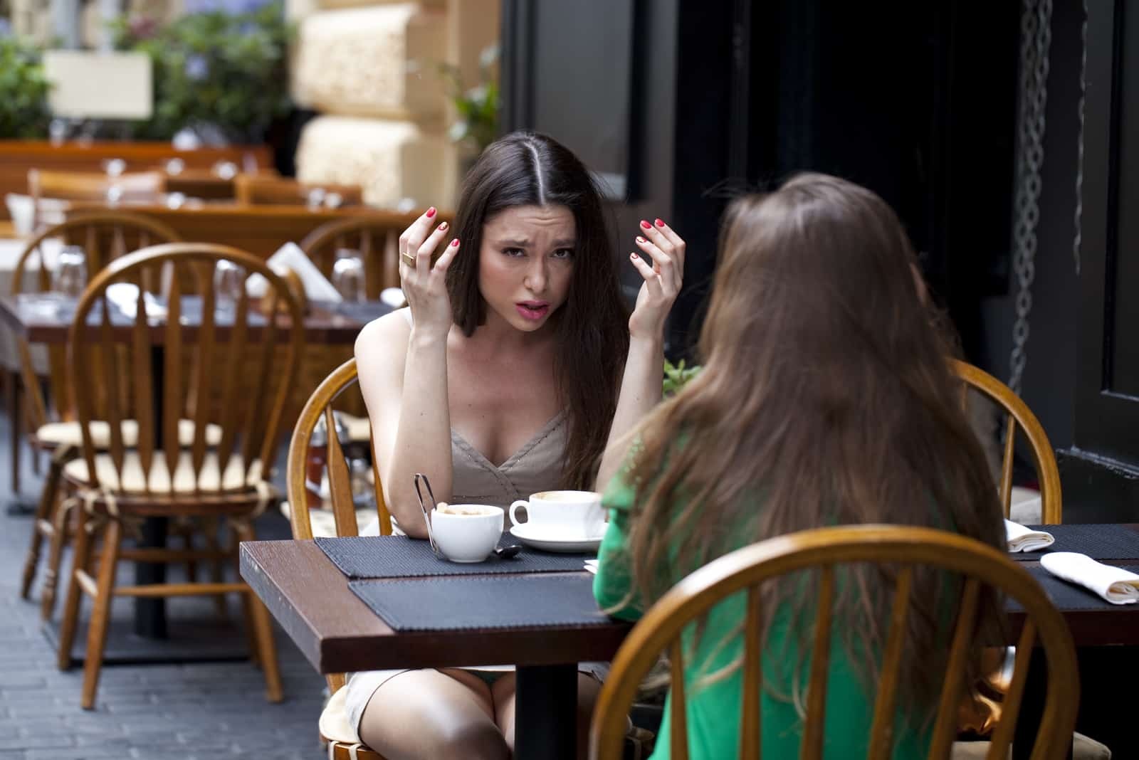 Freunde sitzen auf der Terrasse des Cafés und unterhalten sich ernsthaft