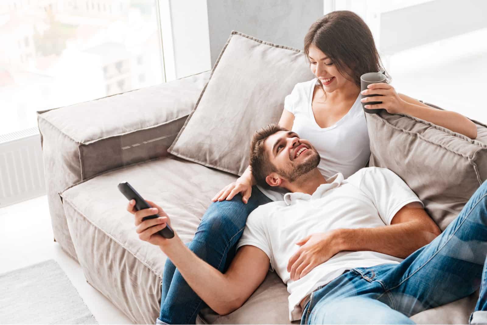 Fröhliches schönes junges Paar, das Kaffee trinkt und zu Hause fernsieht
