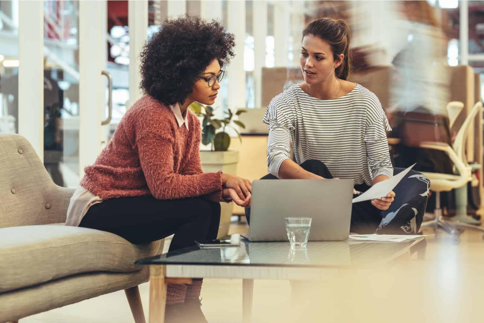 Geschäftsfrauen, die Ideen teilen, die zusammen mit einem Laptop auf Tisch sitzen