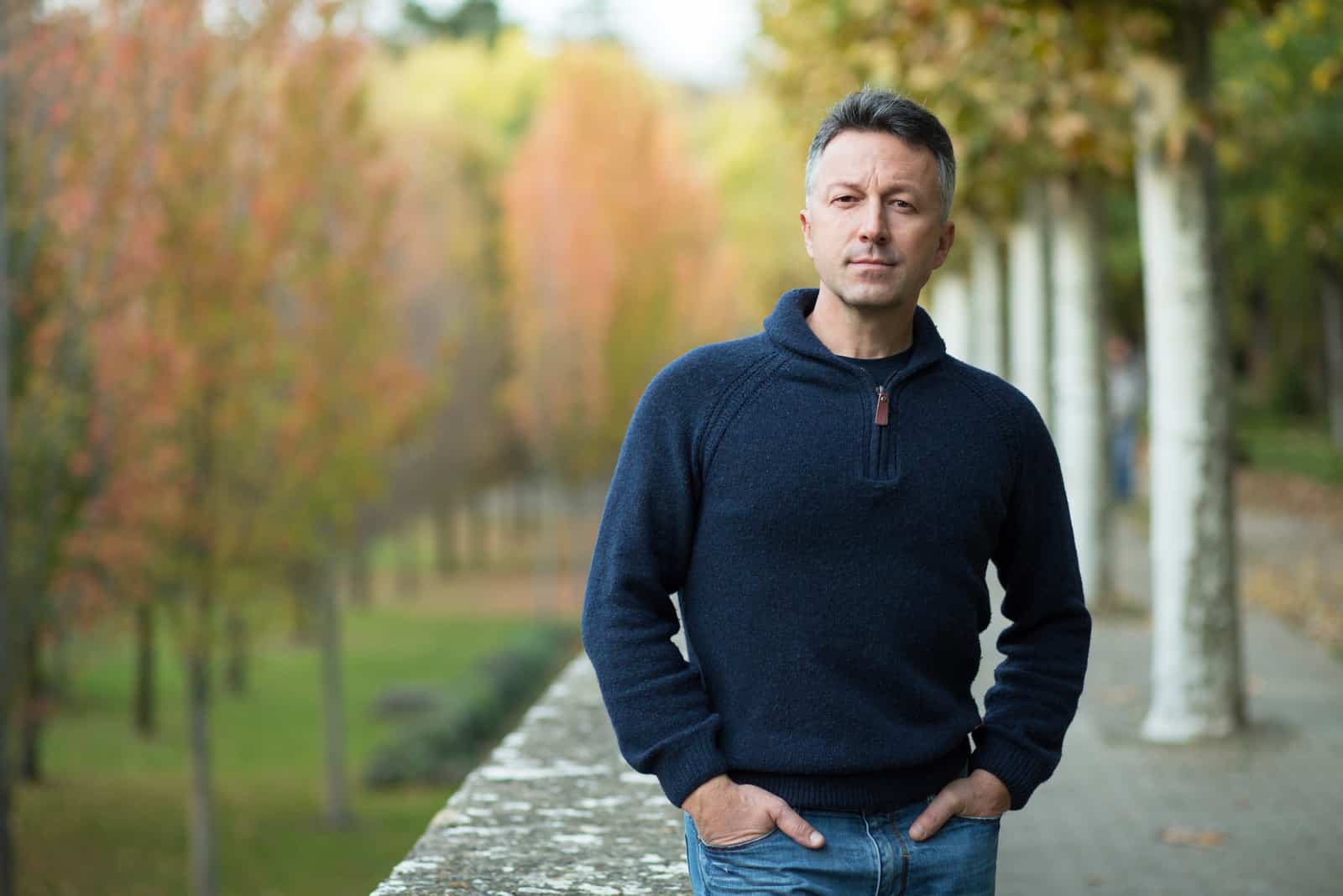 Hübscher Mann mittleren Alters, der Herbstpark geht