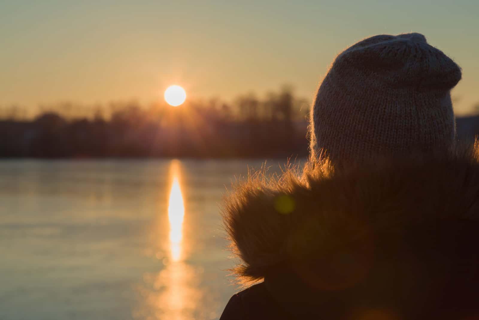 Junge erwachsene Frau, die allein steht und auf orange gelben Sonnenuntergang starrt
