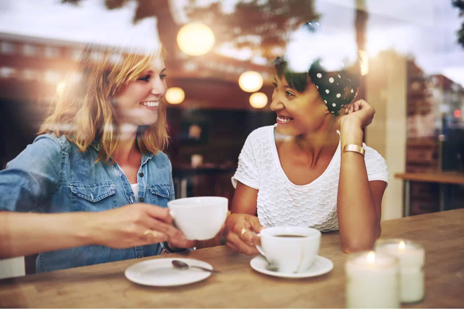 In einem Café hinter der Bar sitzen zwei schöne Frauen, die Kaffee trinken und reden