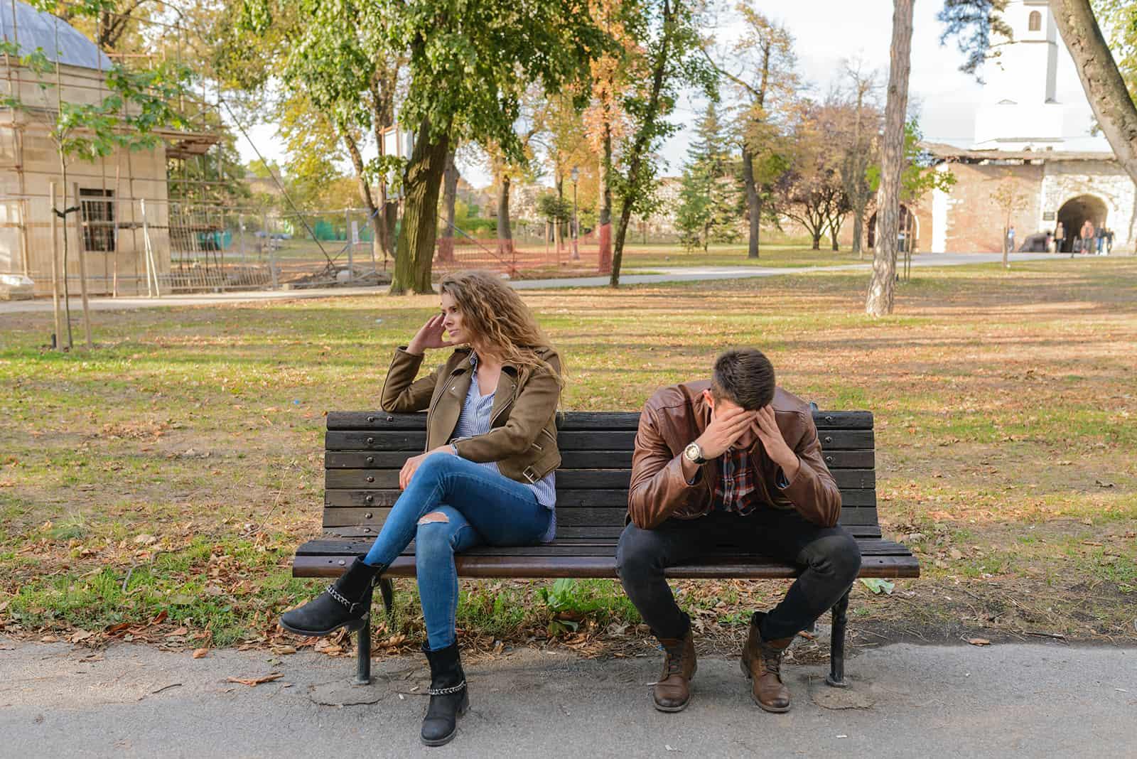 verärgertes Paar, das auf der Bank sitzt und sich voneinander abwendet