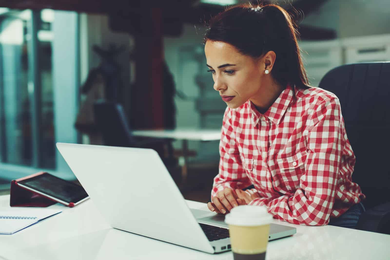 Junge Frau, die am Laptop im Büro arbeitet