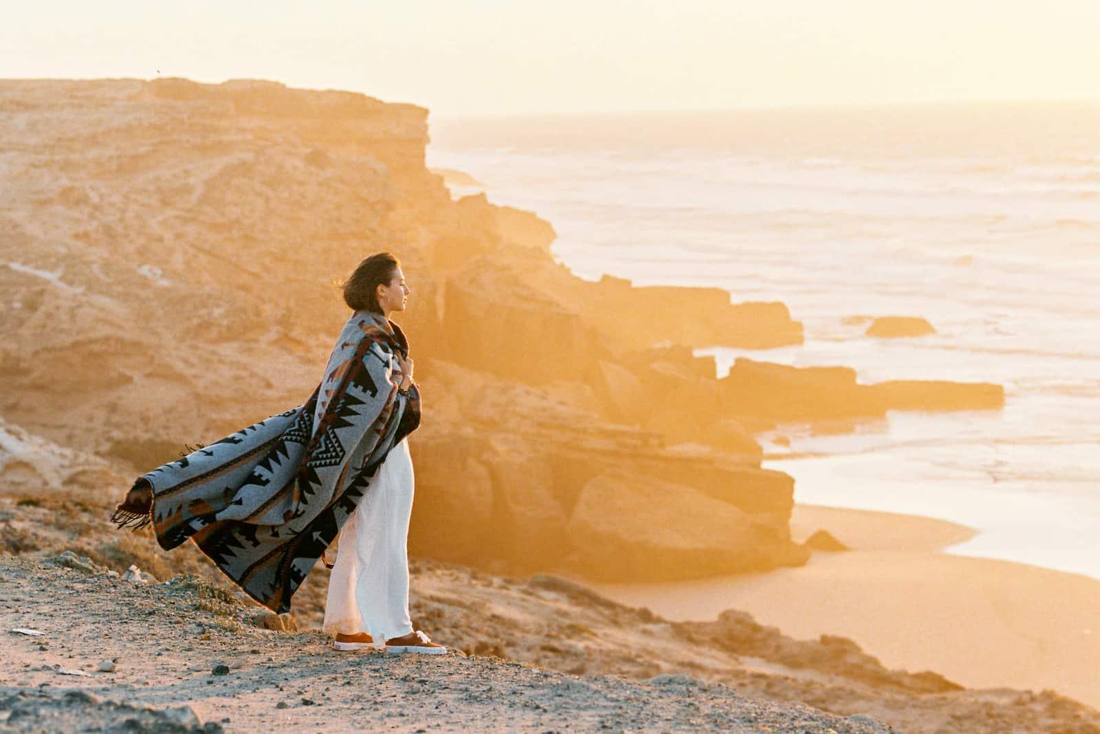 Junge Frau mit fliegender Decke, die auf Klippenrand steht und zum Ozean auf Sonnenuntergang schaut
