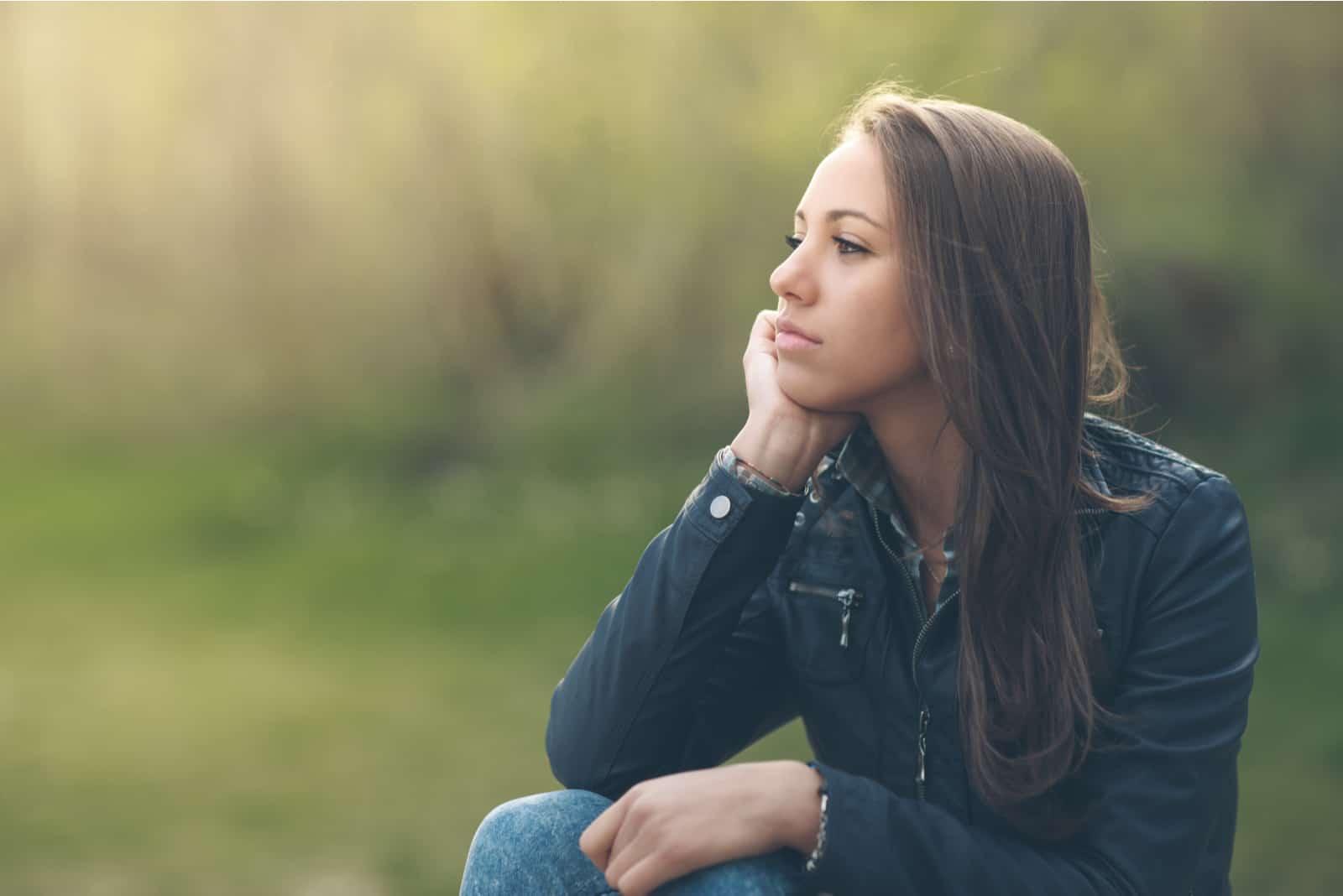 Junge nachdenkliche Frau, die am Park entspannt